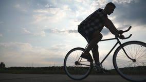 Silhueta da equitação do homem novo na bicicleta do vintage com o céu bonito do por do sol no fundo Ciclismo desportivo do indiví video estoque