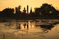 Silhueta da estátua e de pagodes antigos da Buda contra o céu do por do sol em Sukhothai, Tailândia Foto de Stock Royalty Free