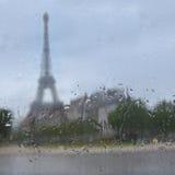 A silhueta da excursão Eiffel através da janela com chuva deixa cair foto de stock