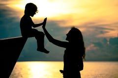 Silhueta da família feliz que que joga na praia no sunse Foto de Stock Royalty Free