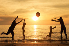 Silhueta da família feliz que que joga na praia no sunse Foto de Stock