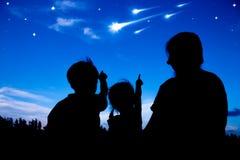 Silhueta da família feliz que senta e que olha o céu em cometas Fotos de Stock Royalty Free