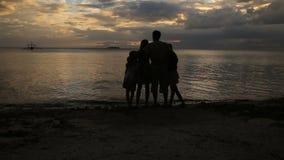 Silhueta da família na praia no por do sol filme