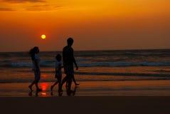 Silhueta da família que anda ao longo da costa imagens de stock