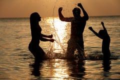 Silhueta da família que tem o divertimento no mar no feriado da praia Fotografia de Stock