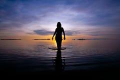 Silhueta da figura da mulher que anda no mar raso Fotos de Stock