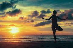 Silhueta da ioga da meditação da mulher na praia do oceano imagens de stock