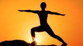 Silhueta da ioga praticando fêmea atlética no monte da montanha, cuidados médicos filme