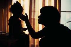 Silhueta da jovem mulher e da sua criança imagem de stock royalty free
