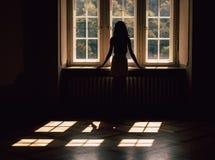 Silhueta da jovem mulher, olhando através da janela foto de stock