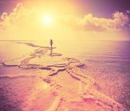 Silhueta da jovem mulher que anda no Mar Morto Fotografia de Stock Royalty Free