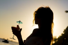 Silhueta da jovem mulher que aprecia as férias a da praia do verão Fotografia de Stock Royalty Free