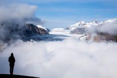 Silhueta da jovem mulher que está sobre Salmon Glacier na Imagens de Stock