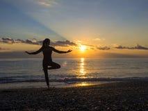 Silhueta da jovem mulher que faz exercícios na praia do mar durante o por do sol Ioga, aptidão e um estilo de vida saudável foto de stock