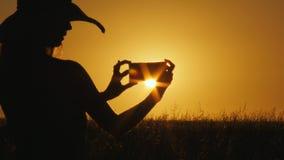 Silhueta da jovem mulher que faz a foto com o smartphone sobre o nascer do sol bonito conceito das férias 4k video estoque