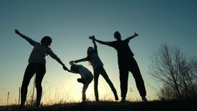 Silhueta da mãe, do pai e das filhas jogando e tendo o divertimento no por do sol filme