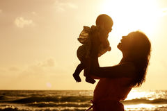 Silhueta da mãe e do bebê no por do sol Imagens de Stock