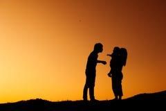 Silhueta da mãe e do filho do pai que jogam fora no por do sol fotografia de stock