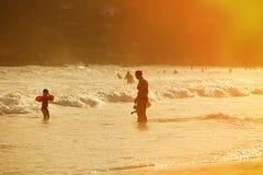 Silhueta da mãe que aprecia uma praia tropical com suas crianças fotografia de stock