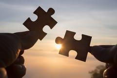 Silhueta da mão que guarda a serra de vaivém com fundo do nascer do sol Símbolo da associação e da conexão Estratégia empresarial foto de stock