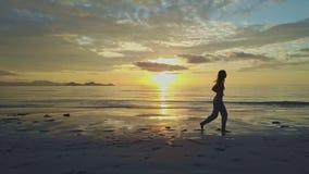 A silhueta da menina anda lentamente ao longo da praia molhada no alvorecer filme