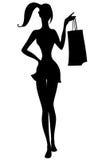 Silhueta da menina bonita com sacos de compras à disposição Fotos de Stock