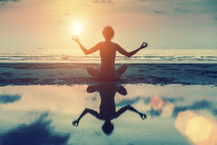 Silhueta da menina bonita que senta-se na praia e que medita na pose da ioga Fotos de Stock Royalty Free