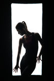 Silhueta da menina delgada que levanta no quadro Fotografia de Stock