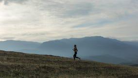 A silhueta da menina magro está movimentando-se em montanhas nevoentas fotos de stock royalty free