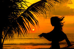 Silhueta da menina na praia no por do sol Imagens de Stock Royalty Free