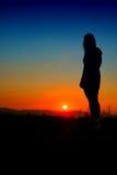 Silhueta da menina no por do sol Fotografia de Stock
