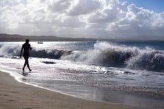 A silhueta da menina que anda ao longo da praia com ondas e ?gua espirra em feriados, mar azul, ondas exp?e ao sol o fundo claro fotos de stock royalty free