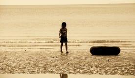 Silhueta da menina que anda na praia Imagem de Stock Royalty Free