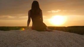 Silhueta da menina que aprecia o por do sol que senta-se na areia, figura da mulher bonita na harmonia com natureza, férias de ve video estoque