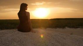 Silhueta da menina que aprecia o por do sol que senta-se na areia, figura da mulher bonita na harmonia com natureza, férias de ve filme