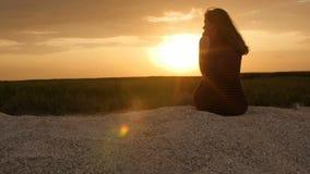 Silhueta da menina que aprecia o por do sol que senta-se na areia, figura da mulher bonita na harmonia com natureza, férias de ve vídeos de arquivo