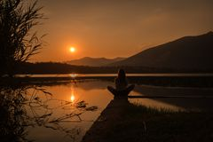 Silhueta da menina que está sobre o amountain do lago na posição da ioga do loto imagem de stock