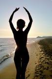 A silhueta da menina que estica e que exercita no watchin da praia imagem de stock royalty free