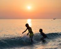 Silhueta da moça dois que salta no mar Imagem de Stock Royalty Free