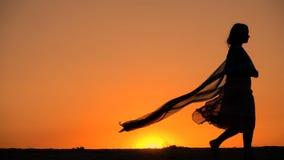 Silhueta da moça que anda contra o por do sol