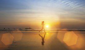 Silhueta da moça que movimenta-se na praia do mar Imagens de Stock