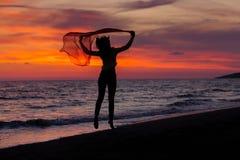 Silhueta da moça, saltando com o pano de seda contra do por do sol do mar imagens de stock royalty free