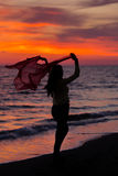 Silhueta da moça, saltando com o pano de seda contra do por do sol do mar fotos de stock royalty free