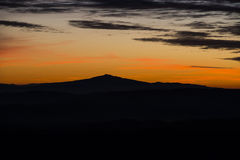 Silhueta da montagem Amiata no por do sol no inverno, Apennines, Umbri Fotos de Stock