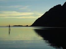 Silhueta da montanha refletida na água Fotos de Stock Royalty Free