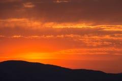Silhueta da montanha sob o céu alaranjado Fotografia de Stock