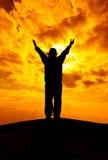 A silhueta da mulher com mãos aumenta acima e reza com luz solar f Fotografia de Stock Royalty Free
