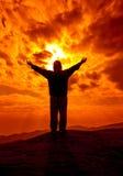 A silhueta da mulher com mãos aumenta acima e reza com luz solar f Imagem de Stock Royalty Free