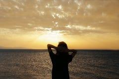A silhueta da mulher com por do sol Imagem de Stock