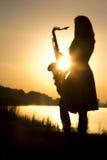 silhueta da mulher com um instrumento de vento musical nas mãos na natureza Fotos de Stock Royalty Free